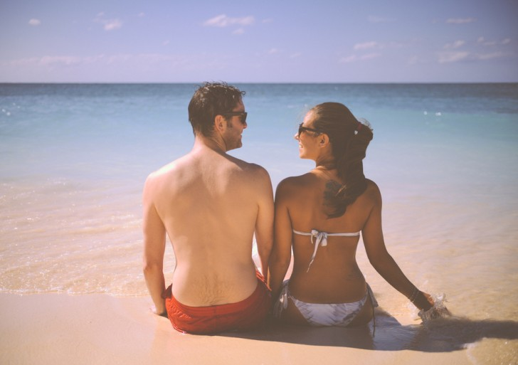 Cute Man And Woman Sitting On A Beach With Sea のコピー