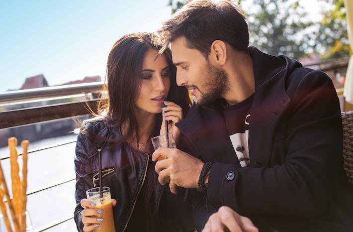 Happy couple drinking orange juice in autumn time